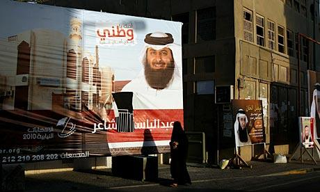 A Bahraini woman walks past election campaign billboards near Manama