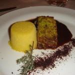 Tournedos di maialino in veste di pistacchi di Bronte con cous cous e salsa al cioccolato di Modica