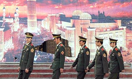 Security guards walk in front of a mural of a mosque in the city of Urumqi in China's Xinjiang province