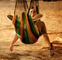 Man relaxing in a hammock on the sandy beaches of The Bahamas