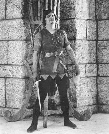 Fairbanks_Robin_Hood_standing_by_wall_w_sword
