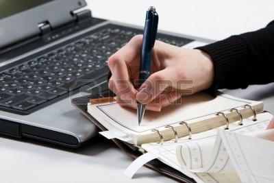 3707930-close-up-of-female-mano-che-regge-la-penna-e-prendere-appunti-in-notebook-con-computer-portatile-a-s