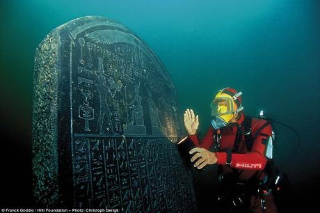 Diver Franck Goddio poses with an inscribed tablet he found in the ruins of Heracleion in Aboukir Bay, Egypt.