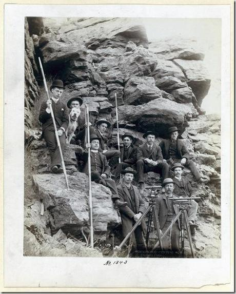 Title: Deadwood Central R.R. Engineer Corps Outdoor group portrait of ten railroad engineers and a dog, posing with surveyors' transits on tripods and measuring rods, on the side of a mountain. Most of the men are sitting; all are wearing suits and hats. [1888] Repository: Library of Congress Prints and Photographs Division Washington, D.C. 20540