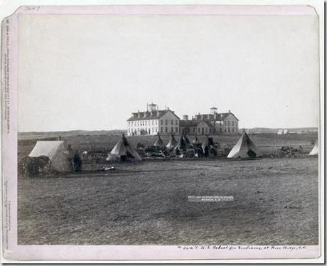 Title: U.S. School for Indians at Pine Ridge, S.D. Small Oglala tipi camp in front of large government school buildings in open field. 1891. Repository: Library of Congress Prints and Photographs Division Washington, D.C. 20540