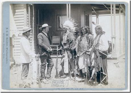 Title: The Interview. Standing Elk, No. 1; Running Hog, No. 2; Little Wolf, No. 3; Col. Oelrich, No. 4; Interpreter, No. 5 Three Cheyenne men wearing ceremonial clothing and holding rifles, greeting a Euro-American man in a suit and his interpreter in front of a building. [between 1887 and 1892] Repository: Library of Congress Prints and Photographs Division Washington, D.C. 20540