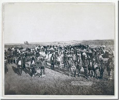 Title: At the Dance. Part of the 8th U.S. Cavalry and 3rd Infantry at the great Indian Grass Dance on Reservation Group portrait of Big Foot's (Miniconjou) band and federal military men, in an open field, at a Grass Dance on the Cheyenne River, S.D.--on or near Cheyenne River Indian Reservation. 1890. Repository: Library of Congress Prints and Photographs Division Washington, D.C. 20540
