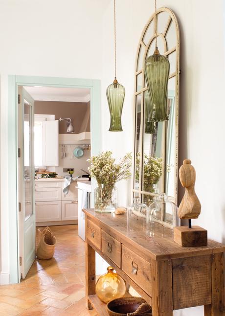 recibidor de estilo rustico con un gran espejo y lamparas de estilo modernista