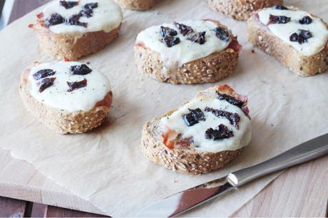 Bruschette con pane tirolese, provola dolce, speck e prugne della California