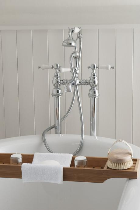 Victorian-style taps adorn the end of a freestanding, roll-top bath