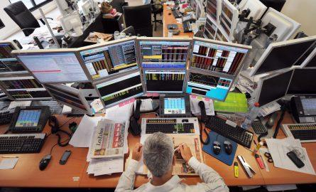 A trader has lunch in front of computers screens on August 19, 2011 at the office of the French investment company Aurel BGC in Paris. Global stocks tumbled further and safe bet gold surged to new records on August 19, 2011 on mounting fears of fresh g...
