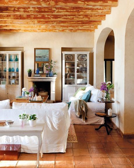 Salón con sofas blancos, chimeneas y vitrinas. Salón en tonos claros con dos alacenas a cada lado de la chimenea