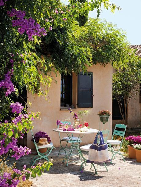Terraza en el porche con mesa y sillas en verde agua marina. Sillas y mesa de hierro rodeadas macetas y plantas en el jardín