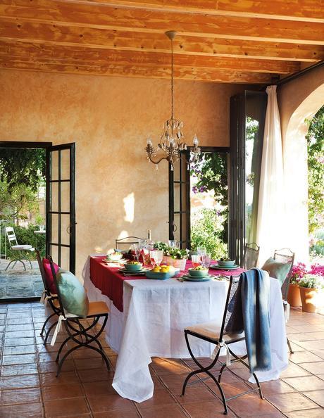 Comedor de verano en el porche con textiles en rosa y verde agua. Comedor en el porche con detalles en verde y fucsia y una lámpara de araña