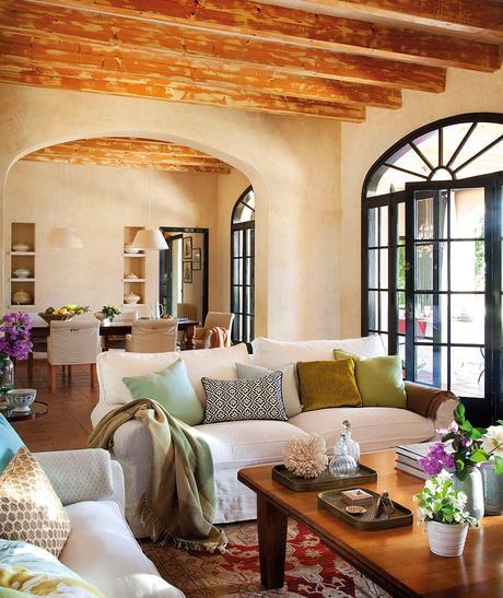 Salón con sofás blancos y comedor al fondo. Salón y comedor con vigas de madera ambos comunican a través de un arco
