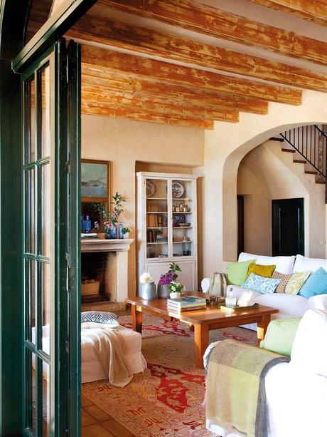 Entrada al salón con chimenea. Rústico salón con vigas de madera, chimenea y cojines de varios colores y estampados sobre los sofás blancos