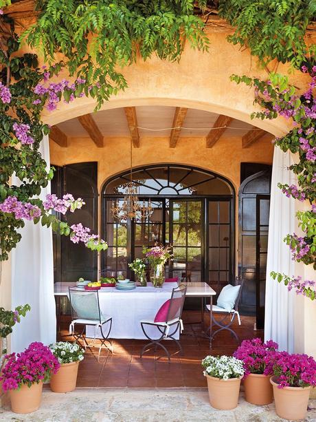 Comedor de verano en el porche. Porche con arcos con cortinas blancas rodeado de plantas
