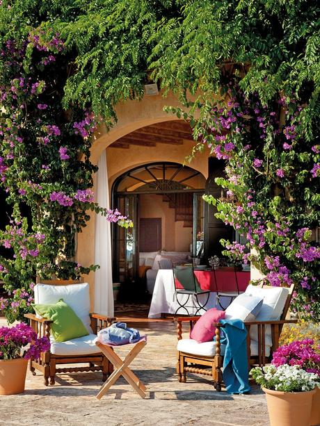 Rincón de estar con butacas y mesa plegable en el porche. Rincón de descanso con butacas de madera con cojines blancos junto al arco que comunica con el porche