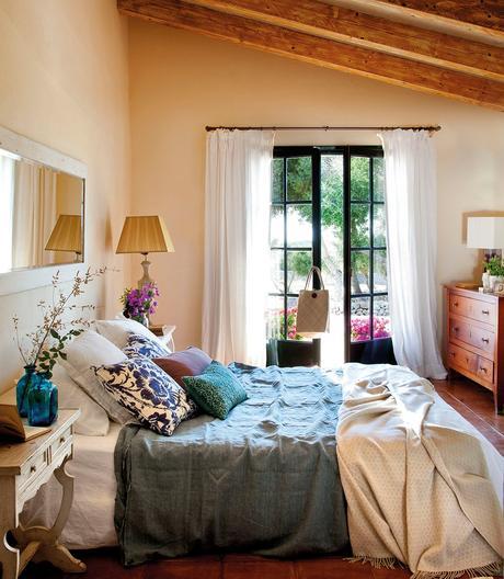 Dormitorio que se comunica al jardín por gran ventanal. Dormitorio principal con un espejo alargado encima de la cama y una puerta acristalada al jardín