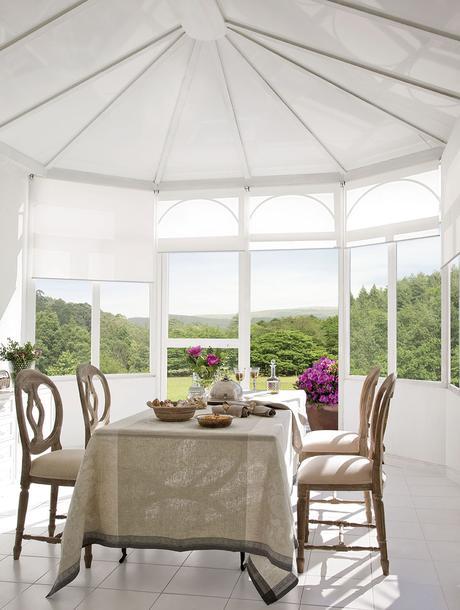 00302846. Comedor en blanco con sillas de madera, mantelería en beige y vistas al jardín_00302846