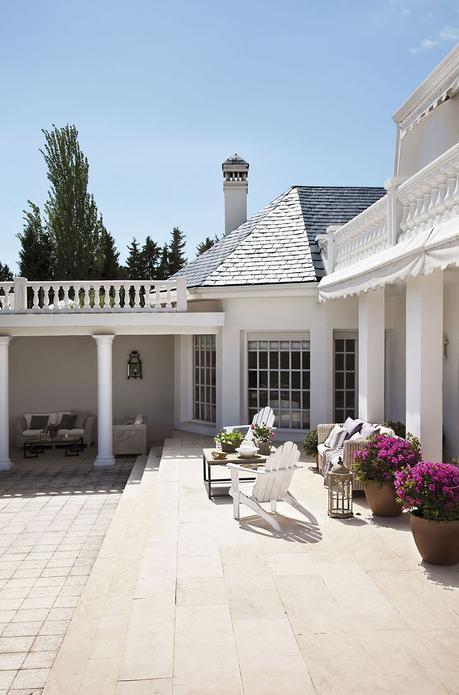 00302837. Fachada de la casa blanca con un porche con muebles de ratán y dos butacas blancas de madera_00302837