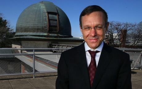 Uomo che sorride con l'osservatorio in background.
